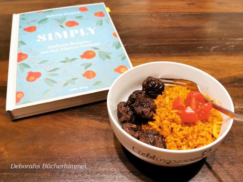Das komplette Gericht Fleischklöße und Paprika-Knoblauch-Reis angerichtet in einer Schüssel zusammen mit dem Kochbuch Simply.