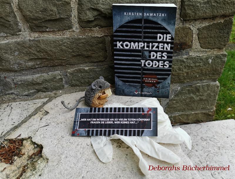 """""""Die Komplizen des Todes"""" von Kirsten Sawatzki auf einer Treppe mit passendem Lesezeichen und der Blogmaus"""