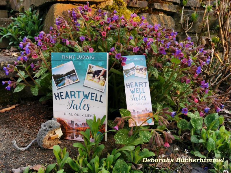 Buch Heartwell Tales von Finny Ludwig mit Lesezeichen und Blogmaus vor Blumen