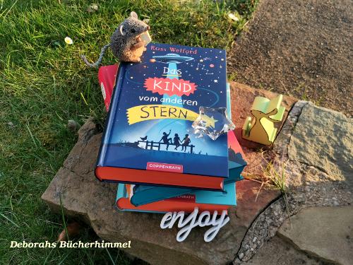 Das Kind vom anderen Stern auf einem Haufen Welford Büchern zusammen mit Blogmaus und Deko.