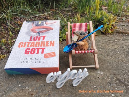 Luftgitarrengott von Herbert Hirschler neben Blogmaus im Liegestuhl und Deko, man sieht den Farbschnitt des Buches