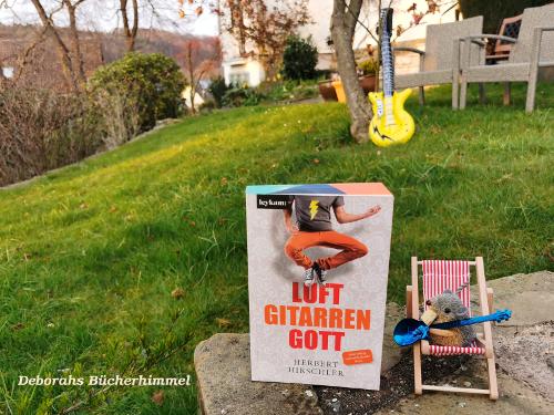 Luftgitarrengott mit Blogmaus auf Liegestuhl im Vordergrund, im Hintergrund die Luftgitarre