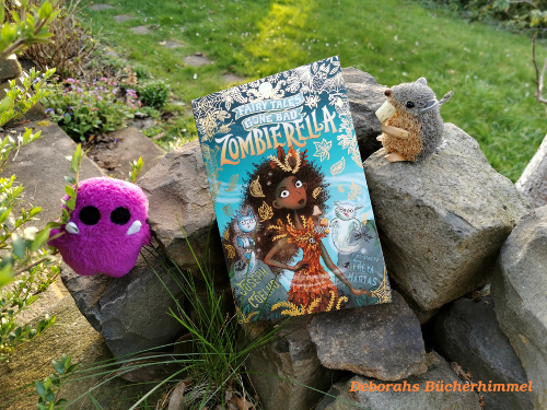 Zombierella from Joseph Coelho lying on stones in the garden, blog mouse and purple monster asides