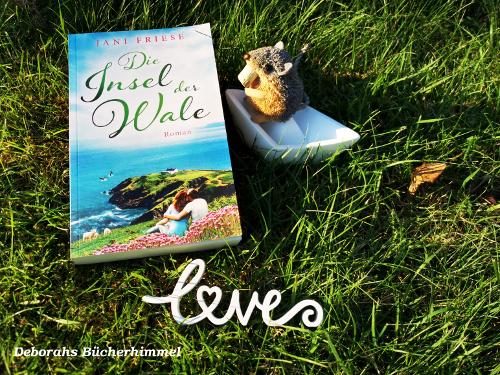"""Buch """"Die Insel der Wale"""" mit Blogmaus, Love-Schriftzug und Boot auf der Wiese."""